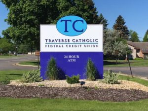 A link to the newest signage image of Traverse Catholic Federal Credit Union sign that says as follows. 24 hour ATM, Traverse Catholic Federal Credit Union, ETCFCU