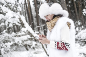 Young woman with mobile phone in winter landscape. Typing a message